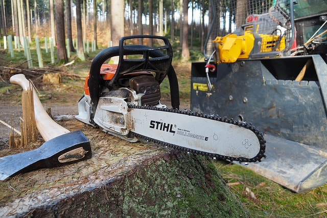 An ax, chainsaw, and bulldozer by a stump in the forest